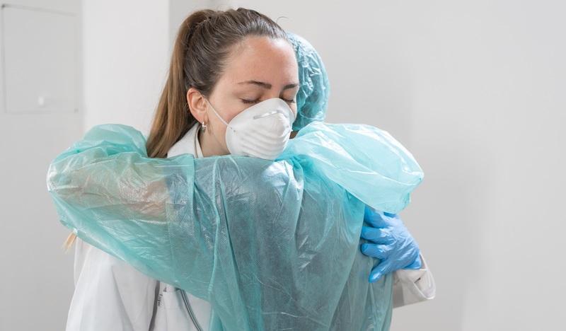 Doctors in PPE hugging