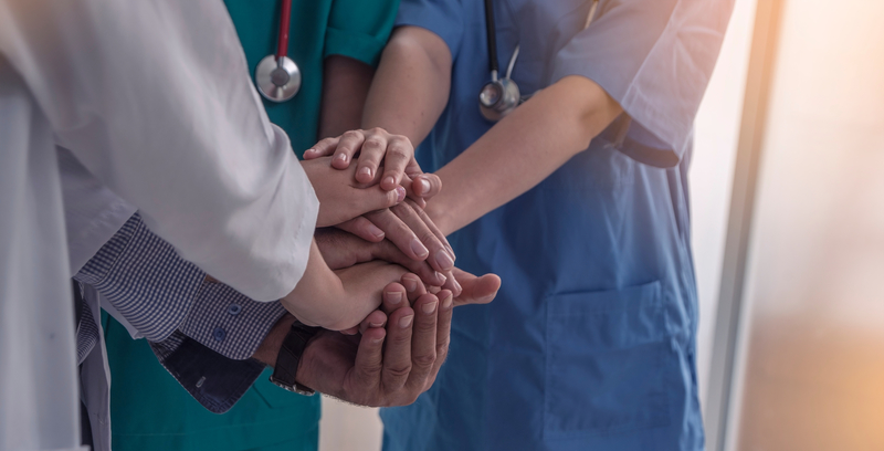 doctors and nurses hold hands