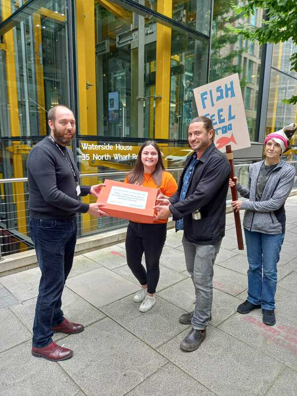 Image shows Allan Ross, the Deputy Head of External Communications at Marks and Spencer accepting the petition presented to him by Sarah (a member of the 38 Degrees team) and Matt (the petition starter).