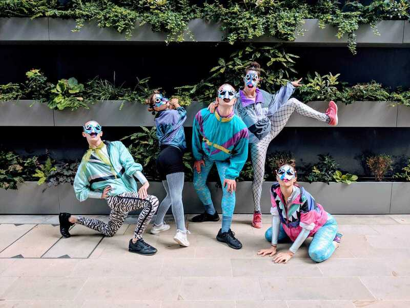 Image shows a group of five dancers, who are wearing face paint and costumes to make them look like salmon.