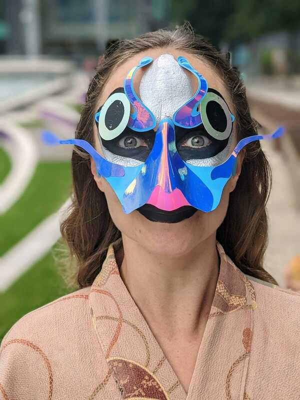 Image shows a close up of one a dancers. She is wearing a blue half-face mask, along with blue and silver face paint so that she looks like a salmon.